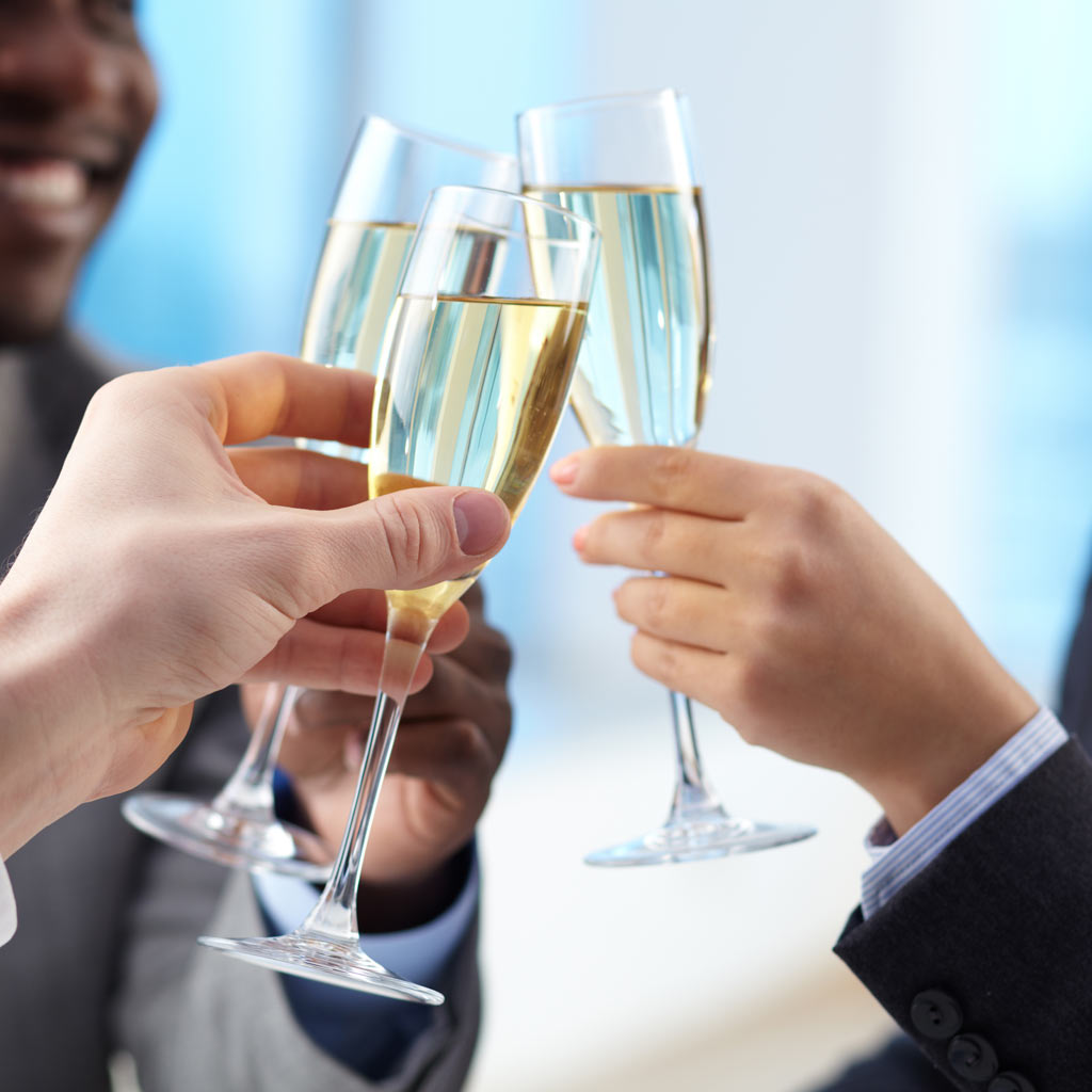 business partners smiling and clinking champagne glasses togther
