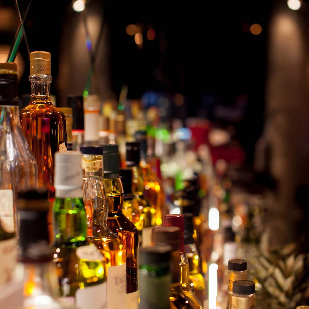 rows of liquor and various bottles of alcohol behind bar