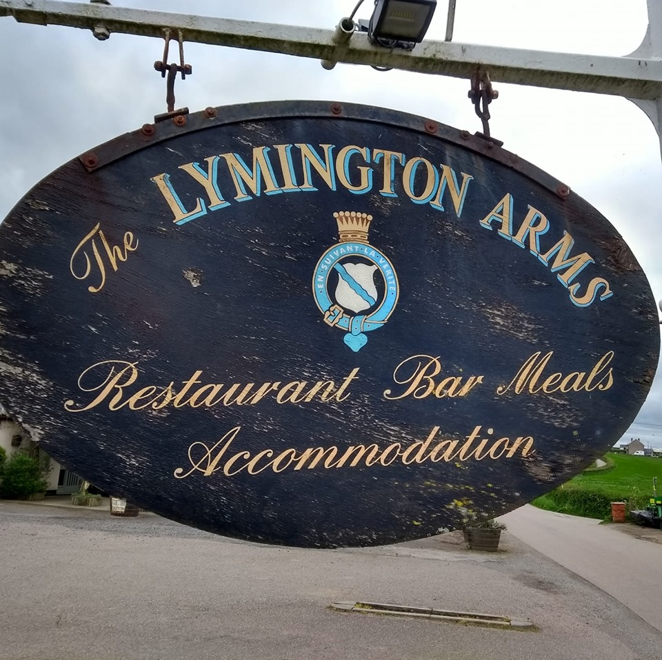 wooden, traditional sign reading The Lymington Arms Restaurant Bar Meals Accomodation with traditional crest in the centre